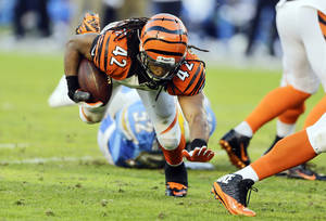 Photo - Cincinnati Bengals running back BenJarvus Green-Ellis keeps on his feet as he rushes against the San Diego Chargers during the second half of an NFL football game Sunday, Dec. 1, 2013, in San Diego. (AP Photo/Lenny Ignelzi)