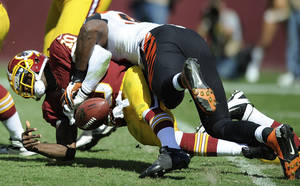 Photo -   Washington Redskins quarterback Robert Griffin III is sacked by Cincinnati Bengals defensive end Michael Johnson during the first half of an NFL football game in Landover, Md., Sunday, Sept. 23, 2012. (AP Photo/Nick Wass)