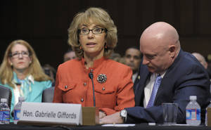 photo - Former Arizona Rep. Gabrielle Giffords, who was seriously injured in the mass shooting that killed six people in Tucson, Ariz. two years ago, sits with her husband Mark Kelly, speaks on Capitol Hill in Washington, Wednesday, Jan. 30, 2013,  before the Senate Judiciary Committee hearing on gun violence.  (AP Photo/Susan Walsh)