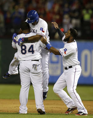 Photo - Texas Rangers' Prince Fielder (84) lifts Adrian Beltre, as Elvis Andrus, right, watches after Beltre hit a game-winning single off of Philadelphia Phillies relief pitcher B.J. Rosenberg in the ninth inning of a baseball game, Tuesday, April 1, 2014, in Arlington, Texas. The hit scored Shin-Soo Choo from second in the 3-2 Rangers win. (AP Photo/Tony Gutierrez)
