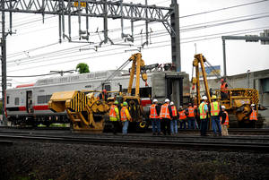 Photo - A derailed Metro-North rail car is hoisted back on to the tracks in Bridgeport. Conn. on Sunday, May 19, 2013. Crews will spend days rebuilding 2,000 feet of track, overhead wires and signals following the collision between two trains Friday evening that injured 72 people, Metro-North President Howard Permut said Sunday. (AP Photo/The Connecticut Post,Brian A. Pounds ) MANDATORY CREDIT