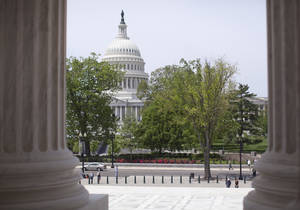 Photo - FILE - In this May 5, 2014, file photo, the U.S. Capitol building is seen through the columns on the steps of the Supreme Court in Washington. The House is poised to act on a bill that would temporarily patch over a multibillion-dollar pothole in federal highway and transit programs while ducking the issue of how to put the programs on sound financial footing for the long term. The bill by House Ways and Means Committee Chairman Dave Camp cobbles together $10.8 billion in pension tax changes, customs fees and money from a fund to repair leaking underground fuel storage tanks to keep the federal Highway Trust Fund solvent through May 2015. A similar bill is pending in the Senate.  (AP Photo/Carolyn Kaster, File)
