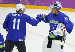 Photo - Slovenia forward Anze Kopitar bumps fists with goaltender Robert Kristan after Slovenia beat Austria 4-0 in a men's ice hockey game at the 2014 Winter Olympics, Tuesday, Feb. 18, 2014, in Sochi, Russia. Slovenia advanced to the quarterfinals. (AP Photo/Julio Cortez)