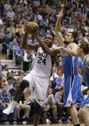 Photo - Utah Jazz's Paul Millsap (24) goes to the basket as New Orleans Hornets' Ryan Anderson (33) defends in the second quarter during an NBA basketball game Friday, April 5, 2013, in Salt Lake City. (AP Photo/Rick Bowmer)