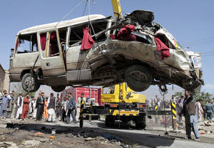 photo -   A damaged bus which was hit by a remote control bomb is lifted by a crane on the outskirts of Kabul, Afghanistan, Tuesday, Aug. 7, 2012. A militant detonated a remote-control bomb Tuesday morning, killing at least eight Afghan civilians who were traveling in a bus just northwest of the Afghan capital, police said. (AP Photo/Musadeq Sadeq)
