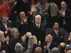 Photo - Phil Jackson waves to the crowd as he is introduced during the first half of an NBA basketball game between the New York Knicks and the Indiana Pacers at Madison Square Garden on Wednesday, March 19, 2014, in New York. Jackson was hired as the president of the Knicks this week. (AP Photo/Seth Wenig)