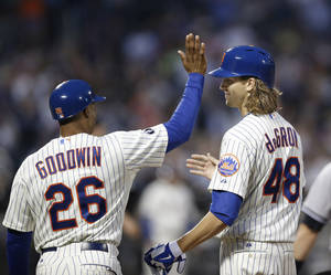 Photo - New York Mets first base coach Tom Goodwin (26) congratulates Mets starting pitcher Jacob deGrom after deGrom hit a third-inning single in a baseball game against the New York Yankees in New York, Thursday, May 15, 2014. (AP Photo/Kathy Willens)