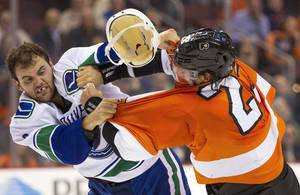 Photo - Vancouver Canucks' Zack Kassian, left, loses his helmet as he fights with Philadelphia Flyers' Luke Schenn, right, during the first period of an NHL hockey game, Tuesday, Oct. 15, 2013, in Philadelphia. (AP Photo/Chris Szagola)