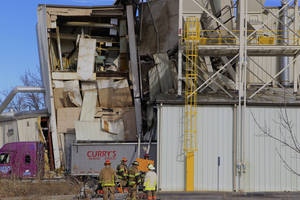 Photo - Firefighters stage outside the International Nutrition plant in Omaha, Neb., Monday, where a fire and explosion took place Jan. 20, 2014. At least nine people have been hospitalized and others could be trapped at the animal feed processing plant. (AP Photo/Nati Harnik)