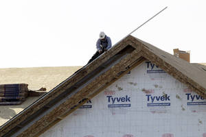 Photo - In this Nov. 28, 2012 photo, a worker constructs a home in Chicago. U.S. builders spent less on construction projects in November, the first decline in eight months, as activity was held back by a big drop in spending on federal projects. (AP Photo/Nam Y. Huh)