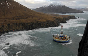 Photo - FILE - In this Jan. 3, 2013 file photo provided by the U.S. Coast Guard, two life rafts sit on the beach adjacent as the conical drilling unit Kulluk sits grounded 40 miles southwest of Kodiak City, Alaska. The united command overseeing the salvage of Royal Dutch Shell PLC drill barge that ran aground on a remote Alaska island will release minimal information on the vessel until an assessment is completed, a spokeswoman said. Shell's drill vessel Kulluk, a round barge with a derrick in its center, ran aground New Year's Eve on the southeast side of Sitkalidak Island near Kodiak Island.(AP Photo/U.S. Coast Guard, Petty Officer 2nd Class Zachary Painter, File)