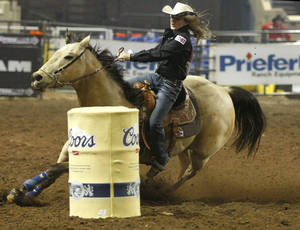 Photo - Carlee Pierce of Stephenville, Texas, competes in barrel racing during the National Circuit Finals Rodeo at State Fair Arena in Oklahoma City, Thursday, March 29, 2012. Photo by Bryan Terry, The Oklahoman
