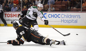 Photo - Dallas Stars center Ryan Garbutt, top, shoots and scores as Anaheim Ducks defenseman Bryan Allen defends during the first period of their NHL hockey game, Sunday, Oct. 20, 2013, in Anaheim, Calif. (AP Photo/Mark J. Terrill)