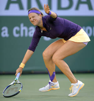 Photo - Victoria Azarenka, of Belarus, winces after returning a shot to Urszula Radwanska, of Poland, during their match at the BNP Paribas Open tennis tournament, Tuesday, March 12, 2013, in Indian Wells, Calif. (AP Photo/Mark J. Terrill)