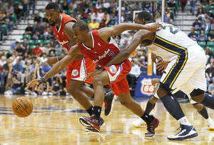 Photo -   Los Angeles Clippers' Chris Paul, center, is held by Utah Jazz's Al Jefferson, right, as Clippers' Deandre Jordan watches during the first half of an NBA preseason basketball game in Salt Lake City, Saturday, Oct. 20, 2012. (AP Photo/George Frey)