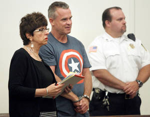 Photo - James Lacroix, 53, center, stands during an appearance with defense attorney Penelope Psomos at Barnstable District Court in Barnstable, Mass., Wednesday, July 16, 2014.  Lacroix, accused of breaking into a home on Cape Cod once owned by John F. Kennedy, told authorities he was looking for singer Katy Perry. (AP Photo/Angela Rowlings, The Boston Herald)  BOSTON OUT