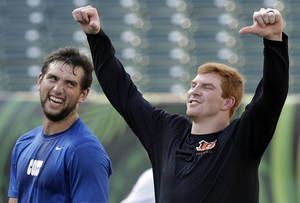 Photo - Indianapolis Colts quarterback Andrew Luck, left, and Cincinnati Bengals quarterback Andy Dalton joke around during warmups before an NFL preseason football game, Thursday, Aug. 29, 2013, in Cincinnati. (AP Photo/Al Behrman)