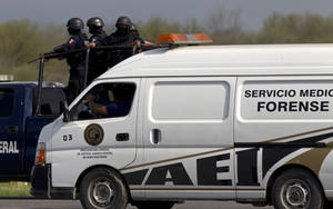 photo -   Federal police stand guard on a vehicle behind a forensic truck containing bodies found on the highway connecting the northern Mexican metropolis of Monterrey to the U.S. border, along the Reynosa-Cadereyta road, in the town of San Juan near the city of Monterrey, Mexico, Sunday, May 13, 2012. Authorities struggled on Monday to identify dozens of people found mutilated and scattered in a pool of blood in a region where Mexico's two dominant drug cartels are trying to outdo each other in bloodshed while warring over smuggling routes. (AP Photo/Christian Palma)