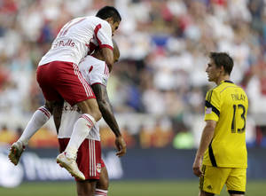 Photo - New York Red Bulls' Tim Cahill, top, jumps on teammate Thierry Henry after Henry scored a goal on the Columbus Crew during the first half of an MLS soccer match, Saturday, July 12, 2014, in Harrison, N.J. Crew's Ethan Finlay (13) walks by during the celebration. (AP Photo/Julio Cortez)