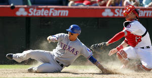 Photo - Texas Rangers' Leonys Martin, left, scores under the tag of Los Angeles Angels catcher Hank Conger on a sacrifice fly in the seventh inning during a baseball game Sunday, Sept. 8, 2013, in Anaheim, Calif. (AP Photo/Alex Gallardo)