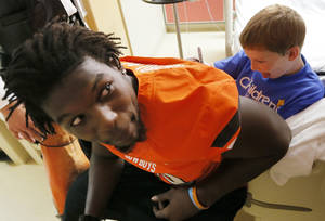 photo - Ernest Cobb, 9, uses the back of Oklahoma State&#039;s Nigel Nicholas to sign an autograph for the players who visited him during a visit by OSU football players to The Children&#039;s Hospital in Oklahoma City, Wednesday, July 11, 2012. Cobb is a patient at The Children&#039;s Hospital. Photo by Nate Billings, The Oklahoman