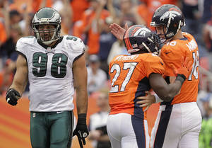 Photo - Denver Broncos quarterback Peyton Manning (18) and running back Knowshon Moreno (27) greet each other on the field after a touchdown against the Philadelphia Eagles in the third quarter of an NFL football game, Sunday, Sept. 29, 2013, in Denver. (AP Photo/Joe Mahoney)