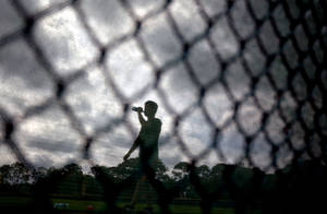 photo -   Baltimore Orioles pitcher Tsuyoshi Wada, of Japan, is seen through mesh fencing as he takes a drink of water during a workout as pitchers and catchers report to spring training baseball Saturday, Feb. 18, 2012, in Sarasota, Fla. (AP Photo/David Goldman)