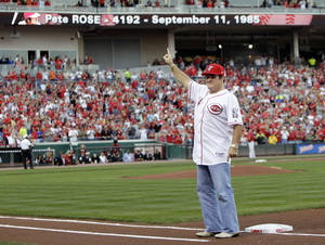 Photo - FILE - In this Sept. 11, 2010, file photo, former Cincinnati Reds great Pete Rose stands on first base as he acknowledges the crowd during ceremonies celebrating the 25th anniversary of Rose breaking Ty Cobb's hit record prior to a baseball game between the Reds and Pittsburgh Pirates in Cincinnati. Rose may have a role to play in next year's All-Star game in Cincinnati despite his lifetime ban from baseball. The career hits leader generally is not allowed in any areas of major league ballparks not open to fans. (AP Photo/Al Behrman, File)