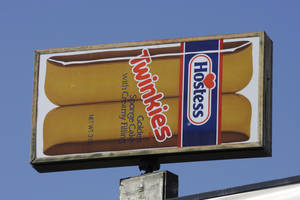 Photo - FILE - A Hostess Twinkies sign is shown at the Utah Hostess plant in Ogden, Utah, in this Nov. 15, 2012 file photo.  Hostess Brands Inc. says it's in talks with more than 100 parties interested in buying its brands, which include Twinkies, Ding Dongs and Ho Hos. (AP Photo/Rick Bowmer, File)