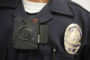 In this Jan. 15, 2014 file photo, a Los Angeles Police officer wears an on-body camera during a demonstration for media in Los Angeles. The fatal police shooting of the unarmed black teenager in Ferguson, Mo. has prompted calls for more officers to wear so-called body cameras, simple, lapel-mounted gadgets that record the interactions between the public and law enforcement. (AP Photo/Damian Dovarganes, File)