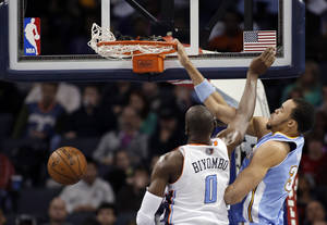 Photo - Denver Nuggets' JaVale McGee (34) dunks over Charlotte Bobcats' Bismack Biyombo (0) during the first half of an NBA basketball game in Charlotte, N.C., Saturday, Feb. 23, 2013. (AP Photo/Bob Leverone)