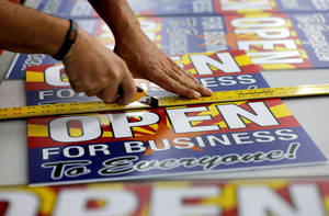 "Photo -      Tom Cushing, a production expert at Fast Signs, cuts down a sheet of anti-Senate Bill 1062 signs that read ""Open For Business To Everyone,"" in Phoenix.  AP Photo  <strong>Matt York - AP</strong>"