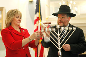 Photo - Gov. Mary Fallin and Rabbi Ovadia Goldman light a candle on a commemorative menorah Friday at the state Capitol. Photo by David McDaniel, The Oklahoman