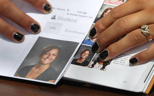 Photo - Wasatch High School sophomore Shelby Baum, 16, points to yearbook proof, left, and her altered school yearbook photo, right, Thursday, May 29, 2014, in Heber City, in Utah. A group of Utah high school students, including Baum, said they were shocked and upset to discover their school yearbook photos were digitally altered, with sleeves and higher necklines drawn on to cover up bare skin.  (AP Photo/Rick Bowmer)
