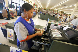 Photo - Tabatha Smith, a full-time employee at Hobby Lobby, works at a cash register at the  6104 W. Reno store. Hobby Lobby on Monday announced a companywide wage increase. <strong>PAUL B. SOUTHERLAND - PAUL B. SOUTHERLAND</strong>