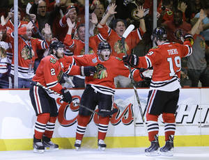 Photo - Chicago Blackhawks right wing Patrick Kane (88) celebrates with center Jonathan Toews (19) and defenseman Duncan Keith (2) after scoring a goal against the Boston Bruins in the second period during Game 5 of the NHL hockey Stanley Cup Finals, Saturday, June 22, 2013, in Chicago. (AP Photo/Nam Y. Huh)