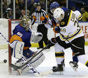 Photo - Boston Bruins' Jordan Caron, right, and New York Islanders' Calvin de Haan scuffle for the puck in front of goalie Kevin Poulin, left,  during the first period of the NHL hockey game, Monday, Jan. 27, 2014, in Uniondale, New York. (AP Photo/Seth Wenig)