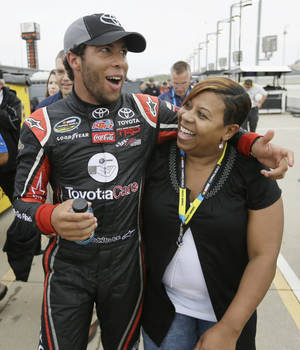 Photo - Darrell Wallace Jr. celebrates with his mom Desiree Wallace after winning the pole position during qualifying for the NASCAR Truck Series auto race, Friday, July 11, 2014, at Iowa Speedway in Newton, Iowa. (AP Photo/Charlie Neibergall)