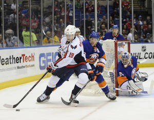 Photo - Washington Capitals' Nicklas Backstrom (19) controls the puck against New York Islanders' Travis Hamonic (3) as goalie Evgeni Nabokov (20) defends the net from behind   in the first period of an NHL hockey game on Saturday, April 5, 2014, in Uniondale, N.Y. (AP Photo/Kathy Kmonicek)