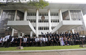 photo - Sri Lankan lawyers sit in protest against the government's impeachment bid to remove chief justice Shirani Bandaranayake at the court complex building in Colombo, Sri Lanka, Friday, Jan. 11, 2013. The lawyers accuse the government of violating the constitution by continuing the impeachment process against Bandaranayake despite court orders against it. They say the impeachment plan is a part of a government move to undermine the independence of the judiciary. (AP Photo/Eranga Jayawardena)