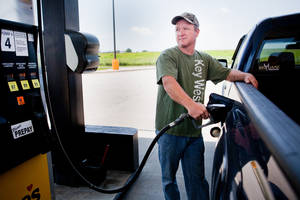 Photo - FILE - In this July 1, 2014 file photo, Lance Thompson pumps gas into his truck at a Love's station in St. Joseph, Mo. The price of oil fell for the ninth straight day Wednesday, July 9, 2014, despite continued turmoil in the Middle East, a drop that could lead to lower gasoline prices for U.S. drivers in the weeks ahead.  (AP Photo/St. Joseph News-Press, Sait Serkan Gurbuz, File)