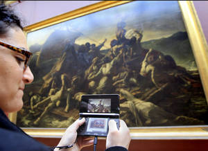 "Photo -   A visitor studies a painting ""The Raft of the Medusa"" by French artist Theodore Gericault 1791 - 1824 with the help of the new audio guide at the Louvre Museum in ParisThursday April 12, 2012. The famed Paris museum is going 3D visual with its electronic guides in a deal with Japan's Nintendo to provide game consoles to help visitors who navigate its labyrinthine halls by the millions each year. The guides, in seven languages, and accompanying headsets cost Euro5 ($6.50) on top of the museum's Euro10 standard admission price. (AP Photo/Jacques Brinon)"
