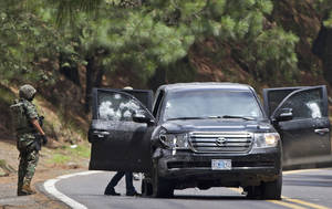 Photo -   FILE - In this Aug. 24, 2012. file photo, an armored U.S. embassy vehicle is checked by military personal after it was attacked by unknown assailants on the highway leading to the city of Cuernavaca, near Tres Marias, Mexico. A senior U.S. official says there is strong circumstantial evidence that Mexican federal police who fired on a U.S. embassy vehicle, wounding two CIA agents, were working for organized crime on a targeted assassination attempt. (AP Photo/Alexandre Meneghini, File)