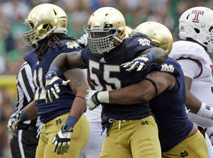 Photo - Notre Dame linebacker Prince Shembo (55) celebrates as he's hugged by teammate Stephon Tuitt after a tackle for a loss against Temple during the first half of an NCAA college football game in South Bend, Ind., Saturday, Aug. 31, 2013. (AP Photo/Michael Conroy)