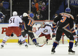 Photo - New York Islanders' Cal Clutterbuck (15) shoots the puck past Columbus Blue Jackets goalie Sergei Bobrovsky (72) to score in the first period of an NHL hockey game on Sunday, March 23, 2014, in Uniondale, N.Y. (AP Photo/Kathy Kmonicek)