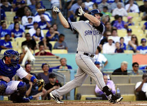 Photo -   San Diego Padres' Chase Headley, right, hits a two-run home run as Los Angeles Dodgers catcher A.J. Ellis watches during the first inning of their baseball game, Monday, Sept. 3, 2012, in Los Angeles. (AP Photo/Mark J. Terrill)