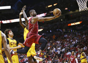 Photo - Miami Heat's Dwyane Wade (3) slides past Cleveland Cavaliers' Anthony Bennett (15) and Anderson Varejao (17) for two points during the first half of an NBA basketball game in Miami, Saturday, Dec. 14, 2013. (AP Photo/J Pat Carter)