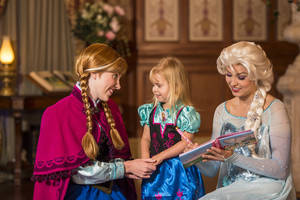 "Photo - This undated image released by Disney shows Disney characters Anna, left, and her sister Elsa, right, from the animated film ""Frozen"" at Princess Fairytale Hall with a young fan at a meet-and-greet at Walt Disney World Resort in Lake Buena Vista, Fla. Wait times to meet the sisters stretches for hours and reservations are snapped up as soon as they become available, part of a frenzy for all things ""Frozen.""  (AP Photo/Disney, Matt Stroshane)"