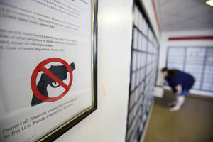 photo - A sign warns that firearms are prohibited in a post office on NW 39 in Oklahoma City. Government buildings are on the short list of exceptions to a new law taking effect Thursday that allows people with a state-issued permit to carry their handguns openly and publicly.  Photo by Steve Gooch, The Oklahoman