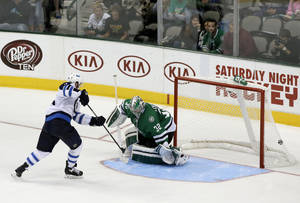Photo - Winnipeg Jets left wing Andrew Ladd (16) scores a shootout goal against Dallas Stars goalie Kari Lehtonen (32), of Finland, in overtime of an NHL hockey game, Saturday, Oct. 26, 2013, in Dallas. The goal helped the Jets to the 2-1 win over the Stars. (AP Photo/Tony Gutierrez)